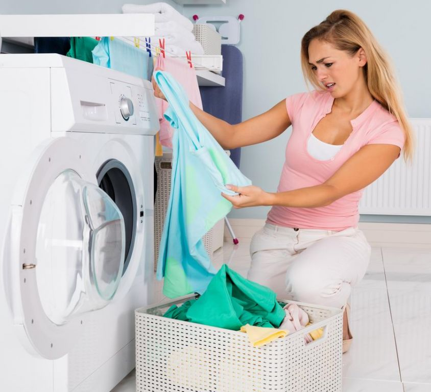 Canva - Woman Looking At Blue T-shirt After Laundering