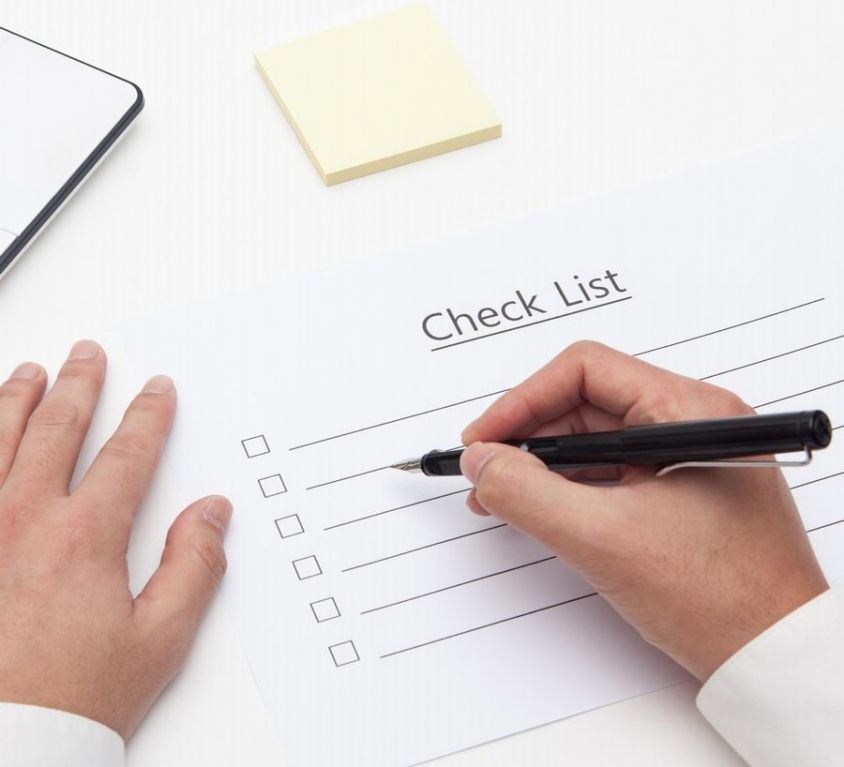 Canva - businessman write on checklist with pencil in office